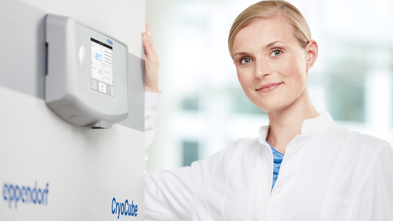 Female laboratory technician in front of lab freezer CryoCube 740hi and VisioNize touch interface.