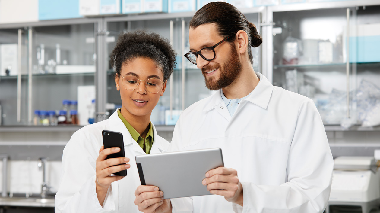 Two laboratory technicians using laboratory software remotely on their portable devices.