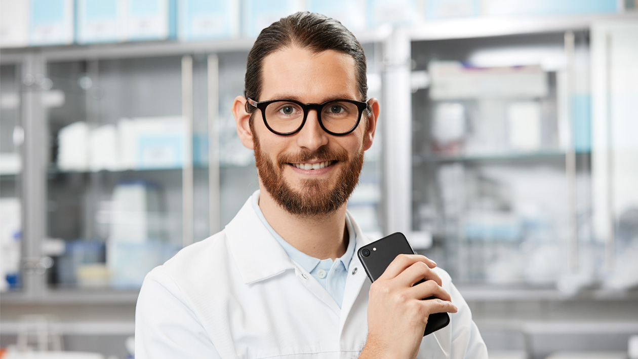 Male laboratory technician with mobile phone using remotely the laboratory software for monitoring lab instruments.