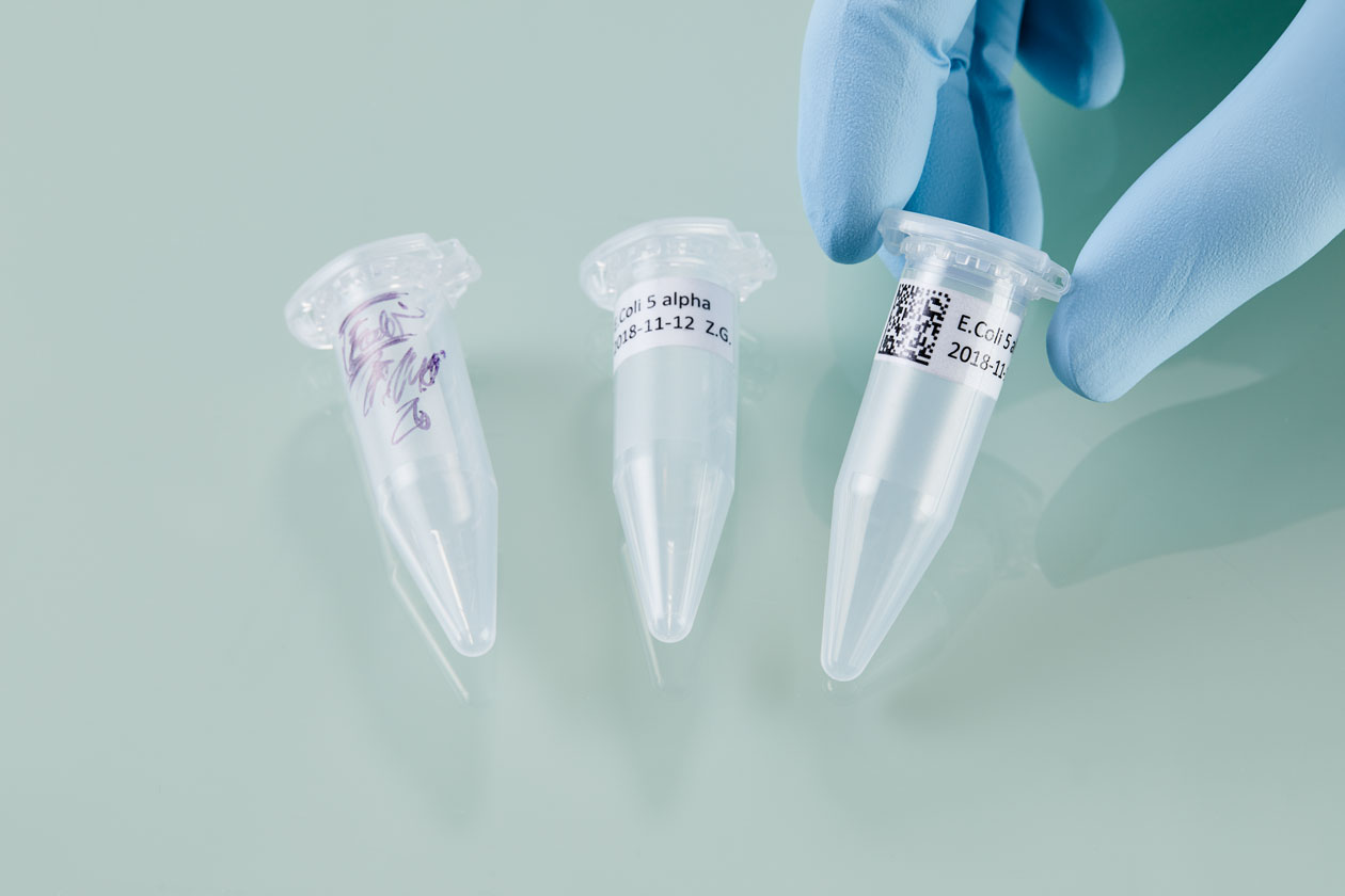 Three laboratory tubes with different types of labels from handwritten to datamatrix code.