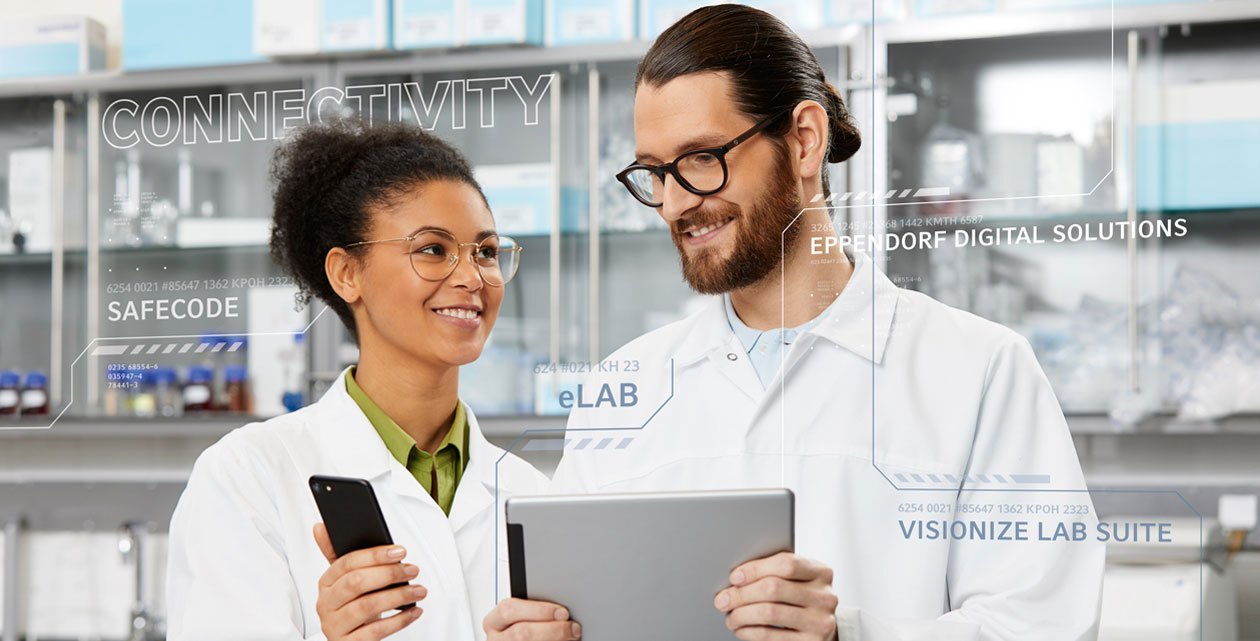 Female scientist in digital lab is holding a smartphone in der hand while male scientist in digital lab is holding a tablet in his hand.