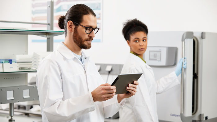 Scientist in laboratory using a tablet to remotely manage the maintenance of lab devices.