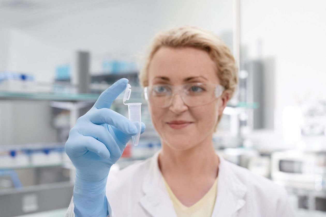 A female scientist in the laboratory checks a conical tube that she has in her hand.
