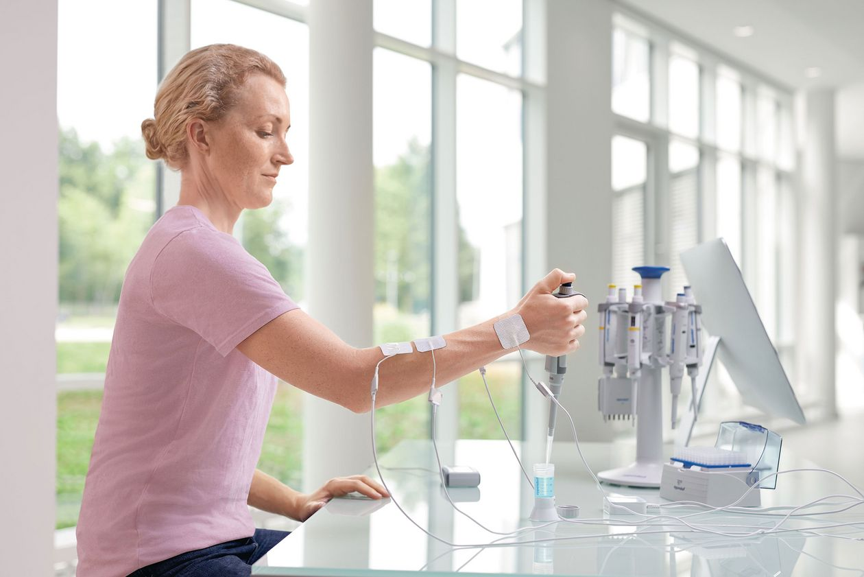 A scientist sits at the bench and is connected with electrodes at the arm to test muscle tension while using an Eppendorf pipette.