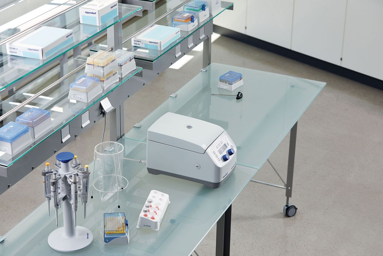 A benchtop centrifuge next to a pipette carousel in an ergonomically designed laboratory.