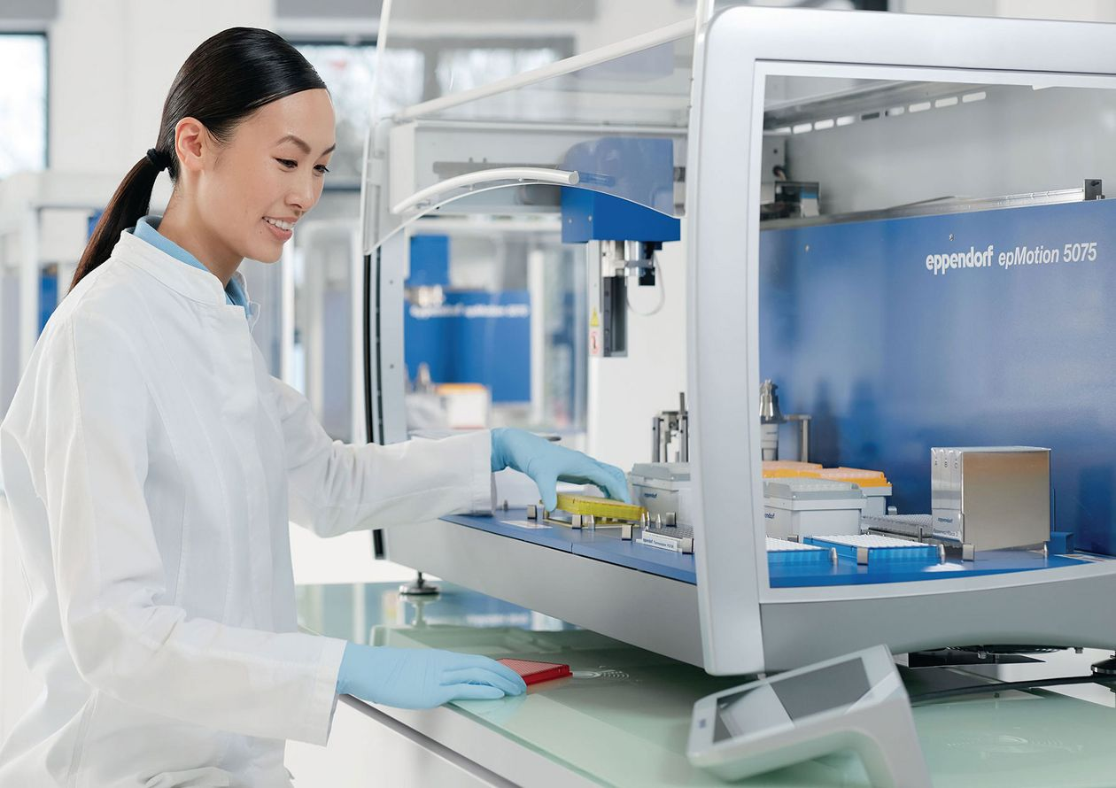 Scientist working ergonomically in the laboratory with an epMotion 5075 automated liquid handling system.