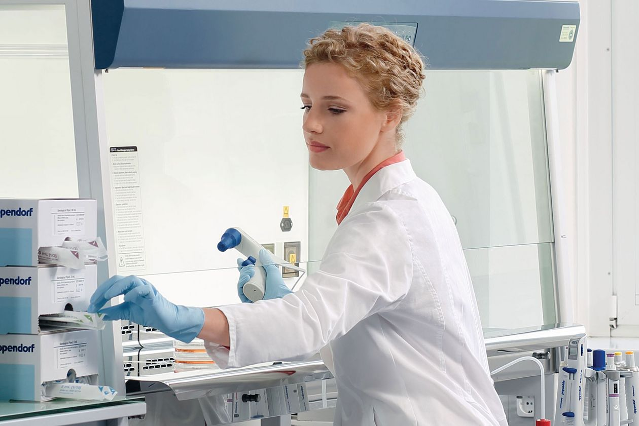 Scientist sitting at a safety cabinet in a laboratory using some Eppendorf packaging boxes.