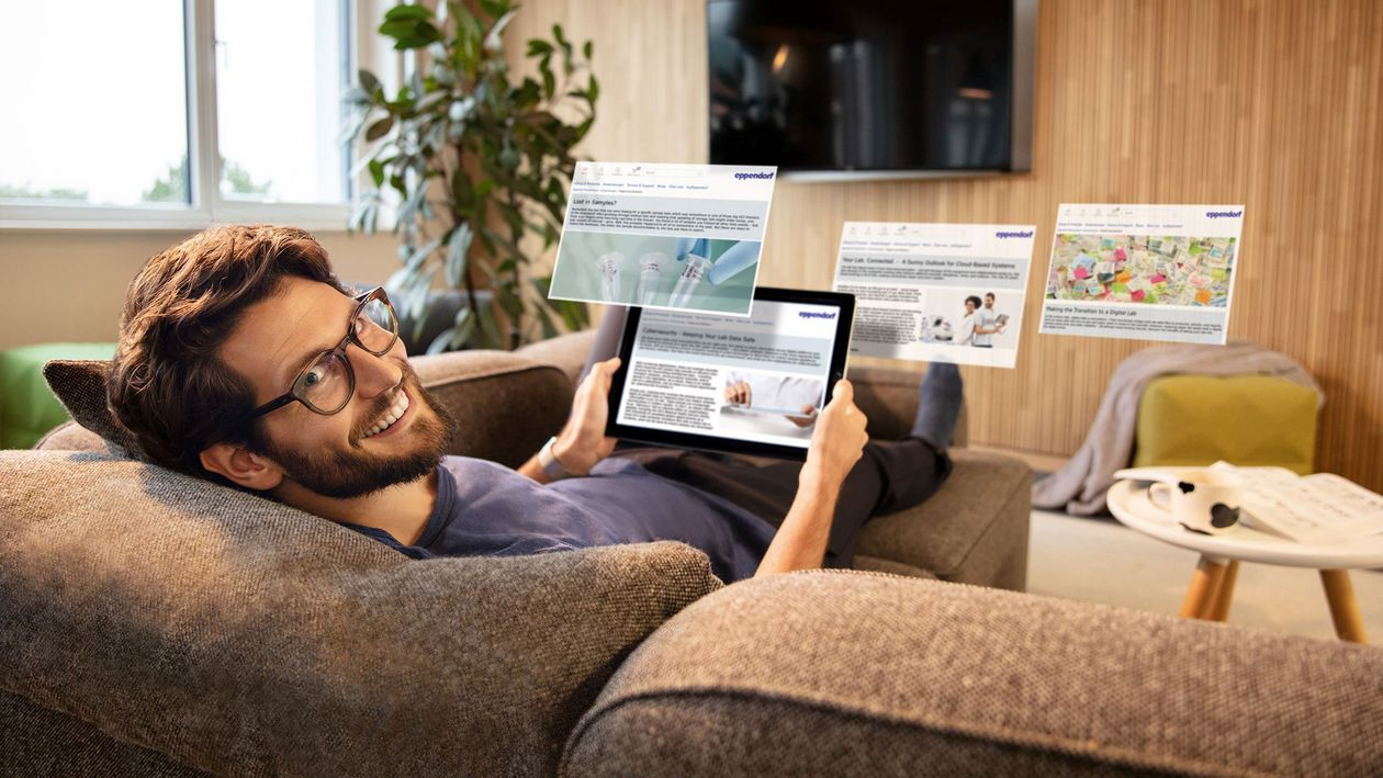 Man lying on a couch using tablet to remotely monitor lab instruments