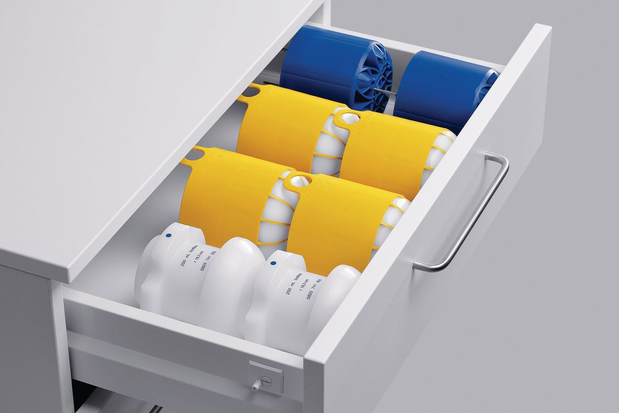 Drawer full of centrifuge adapters in blue, yellow, and white.