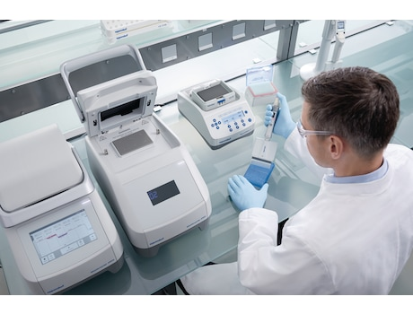 Male laboratory technician works at the bench with PCR, Eppendorf ThermoMixer<sup>&reg;</sup> and dispenses liquid in a plate with a 16-channel pipette