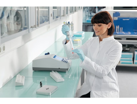Scientist sitting at the bench and filling cuvette for Eppendorf BioPhotometer D30